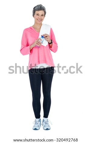 Portrait of woman with towel on shoulder holding bottle against white background - stock photo