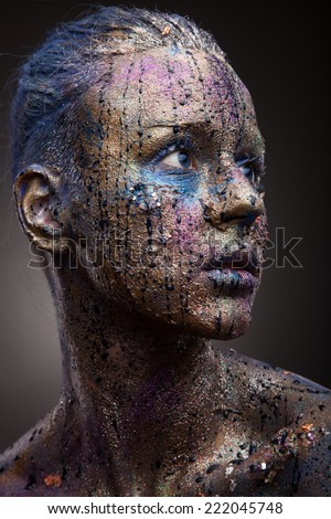 Portrait of woman with unusual paint make-up and face art on dark background