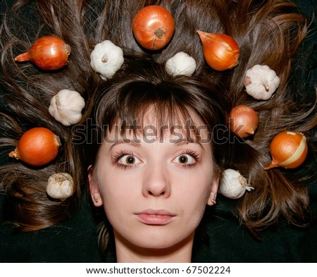 portrait of woman with vegetables in her hair - stock photo