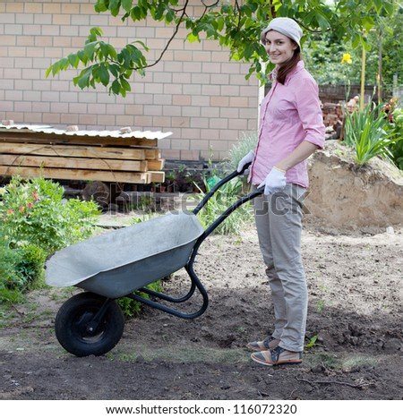 Portrait of woman with wheelbarrow in the garden - stock photo