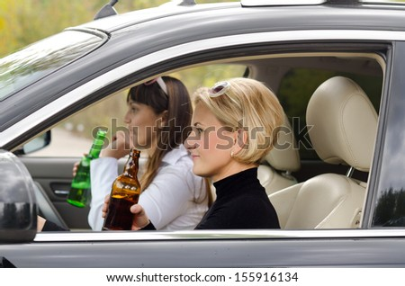 Portrait of women drinking alcohol inside the car - stock photo