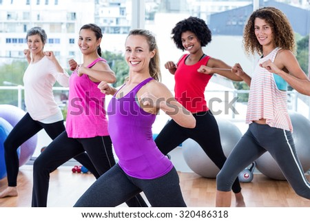 Portrait of women exercising with clasped hands and stretching in fitness studio - stock photo