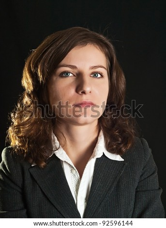 Portrait of women in business suit and white shirt on a black background - stock photo