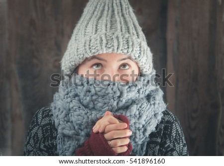 portrait of women in warm hat and scarf warming hands in gloves