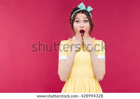Portrait of wondered charming pinup girl in yellow dress with mouth opened over pink background - stock photo