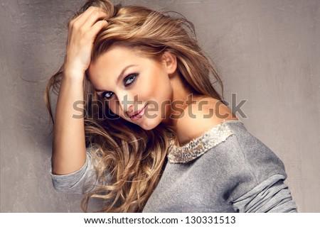 Chân dung tuyệt vời cô gái trẻ tóc vàng với mái tóc dài nhìn vào máy ảnh, mỉm cười.