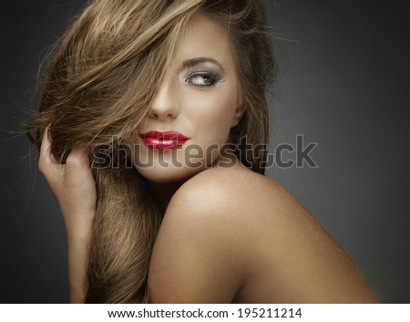 Portrait of wonderful young woman with long hair looking at camera, smiling. - stock photo