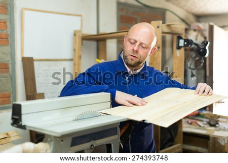 Portrait of woodworker working on a machine at wood workshop - stock photo