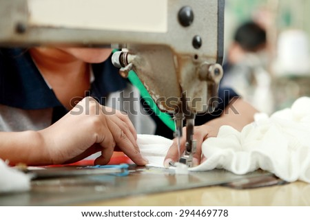 portrait of worker using industrial sewing machine at garment