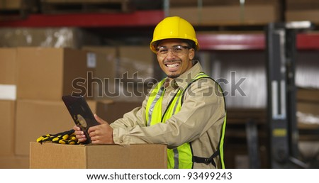 Portrait of worker with digital tablet in warehouse - stock photo