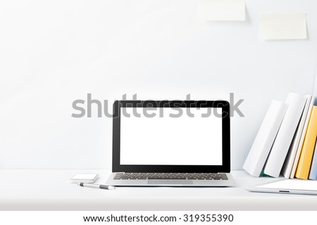 portrait of working desk with laptop, gadget, and books with copy space on white background - stock photo