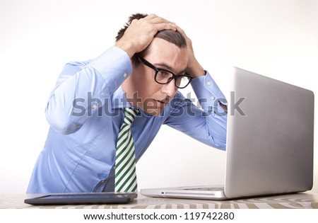 Portrait of worried business man working with laptop. - stock photo