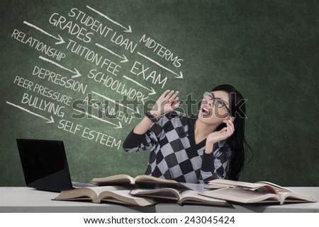 Portrait of worried student having many problems, shot in the class with the text of problems on blackboard - stock photo