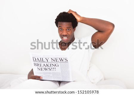 Portrait Of Worried Young African Man Holding Newspaper Sitting On Bed