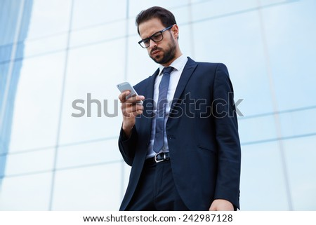 Portrait of worried young business man looking to his cell phone standing near office building - stock photo