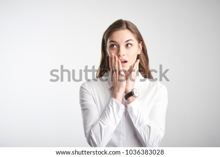 Portrait of worried young woman with hands on her face looking away while standing at isolated white background.