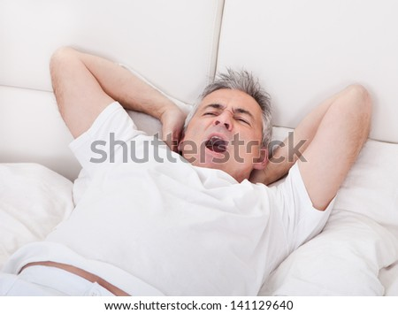Portrait Of Yawning Mature Man Stretching His Arms In Bed - stock photo