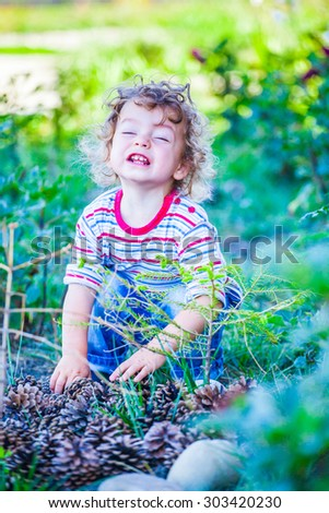 Portrait of 1 year old baby boy playing with pine cones.