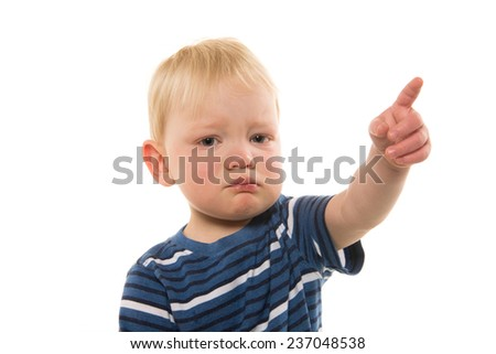Portrait of 2-year-old blond boy crying and pointing with striped shirt on white background - stock photo