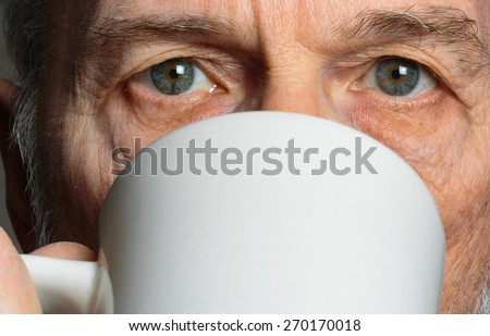 Portrait of 65-year-old Caucasian man drinking coffee from a white mug. - stock photo