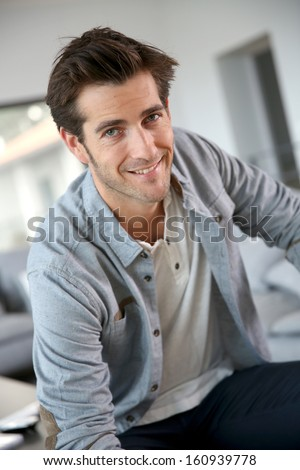 Portrait of 30-year-old man sitting in living-room