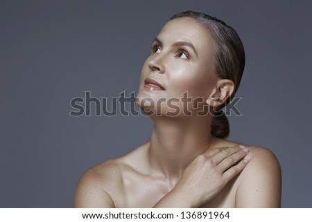Portrait of 40 year old woman with beautiful skin and natural makeup on studio background with copy space over gray - stock photo