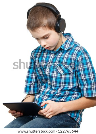 Portrait of 10 years boy wearing headphones using a touch pad - stock photo