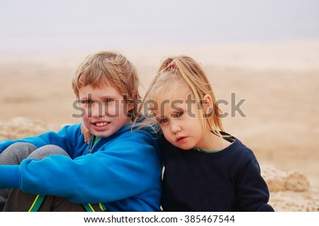 Portrait of 5 years girl with her autistic 8 years old brother outdoors - stock photo