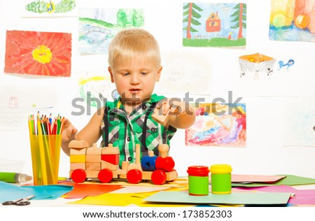 Portrait of 2 years old blond boy in the preschool art class  with pencils toys and blocks