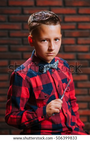 Portrait of 11 years old boy in plaid red shirt with straight razor in the hand on the brick background