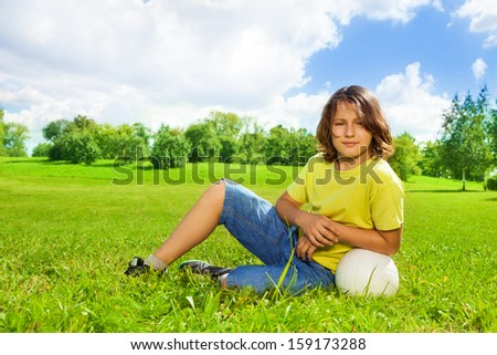 Portrait of 12 years old boy lay in the grass with basketball ball on the field on bright sunny day - stock photo