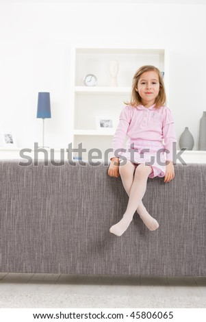 Portrait of 4 years old girl in pink dress, sitting on couch, smiling. - stock photo