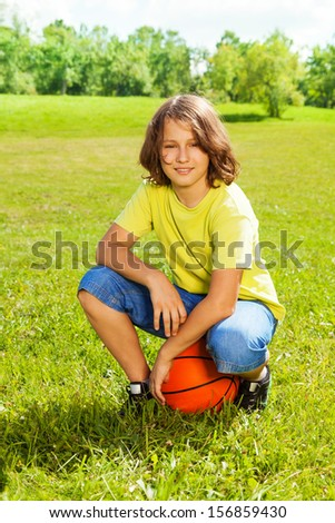 Portrait of 12 years old happy smiling boy sit on squads with basketball ball on the field on bright sunny day - stock photo