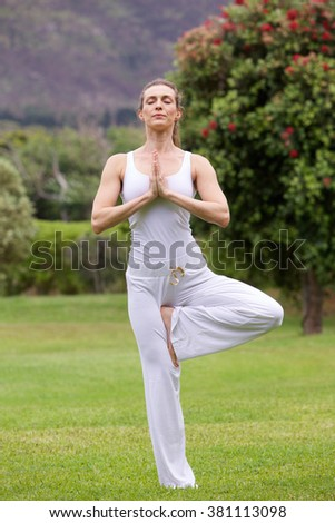 Portrait of yoga woman standing on one leg in park - stock photo