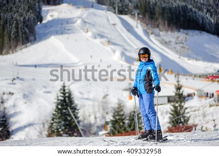 Portrait of young active female skier against ski slopes and ski-lift on background. Woman is wearing helmet skiing glasses gloves and blue ski suit. Winter sports concept. Ski resort - stock photo