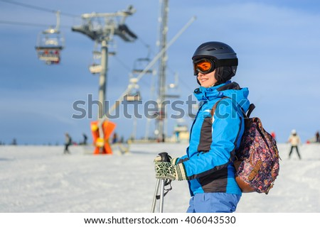 Portrait of young active woman skier at the ski resort on a sunny day against ski-lift. Woman is wearing blue jacket helmet and goggles. - stock photo
