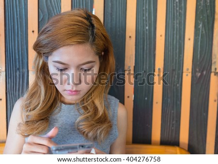 portrait of young adult blond blow hair woman  playing smart phone on hand sitting