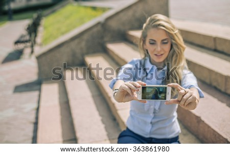 portrait of young adult business woman take picture of themselves while sitting on steps of stairs outdoors in summer city park. lunch time. businesswoman make selfie or look at mirror. Well dressed. - stock photo