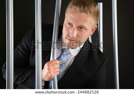 Portrait Of Young Adult Businessman Escaping From Prison - stock photo