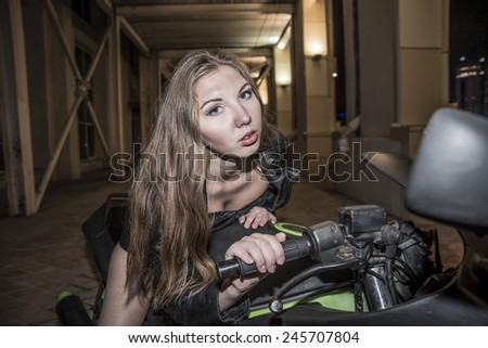 Portrait of young adult caucasian Biker girl in black leather jacket and shorts on motorcycle Cute sexy woman sit on sport bike with long brown hair looking at camera on perspective background  - stock photo