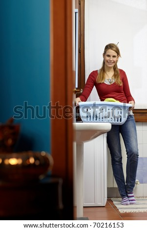 portrait of young adult caucasian woman leaning on washing machine and looking at camera with clothes basket. Vertical shape, front view, copy space - stock photo