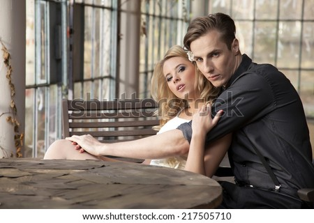 Portrait of young adult couple in love posing in classic elegance clothes to date - stock photo