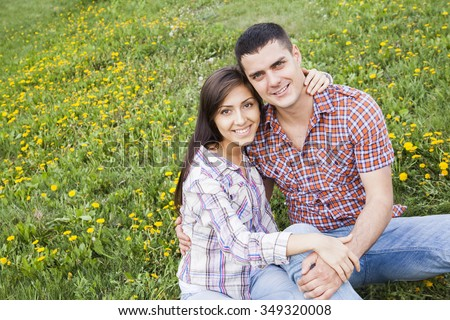 portrait of Young adult couple sit on green grass and yellow spring flowers - dandelion. Man and woman embracing or cuddling against fresh summer meadow. empty copy space for inscription or objects - stock photo