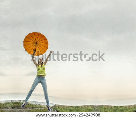 Portrait of Young adult happy teenage girl with colorful orange umbrella jumping up high on empty autumn field meadow copy space nature background Woman wear blue jeans on slim legs  - stock photo