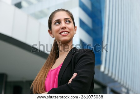 Portrait of young adult hispanic business person with arms crossed, looking at side and smiling - stock photo