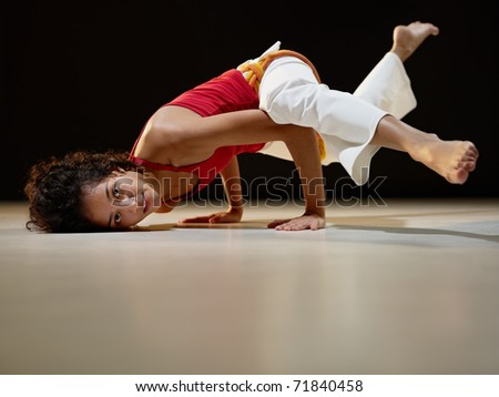 portrait of young adult latin american female doing yoga and capoeira in gym. Horizontal shape, full length, side view, copy space - stock photo