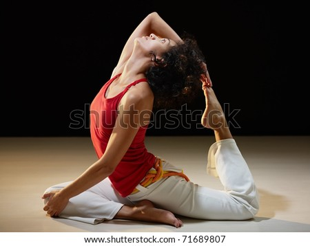 portrait of young adult latin american female doing yoga exercise in gym. Horizontal shape, full length, side view, copy space - stock photo