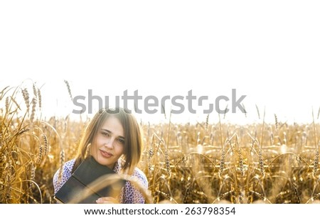 Portrait of young adult latin hispanic girl sitting on reap golden wheat summer field space, reading black book with smiley face Cute asian woman on autumn yellow meadow and sky empty background - stock photo