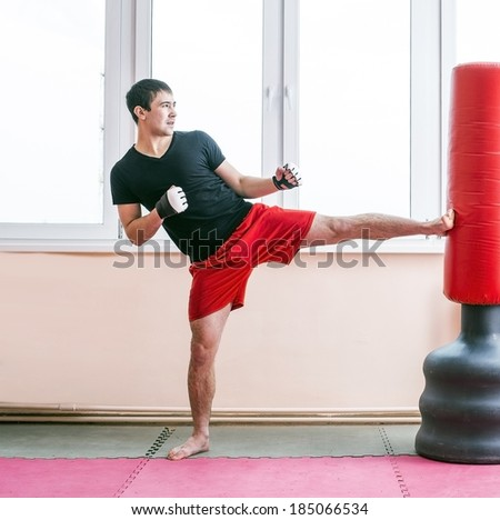 Portrait of young adult latin hispanic man boxer training in gym kick and  boxing punching bag Aggressive asian male inside wall room against window background - stock photo