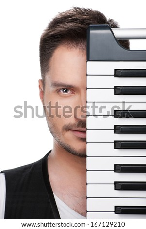 Portrait of young adult musician with half face covered with piano keyboard.  Standing isolated over white background  - stock photo